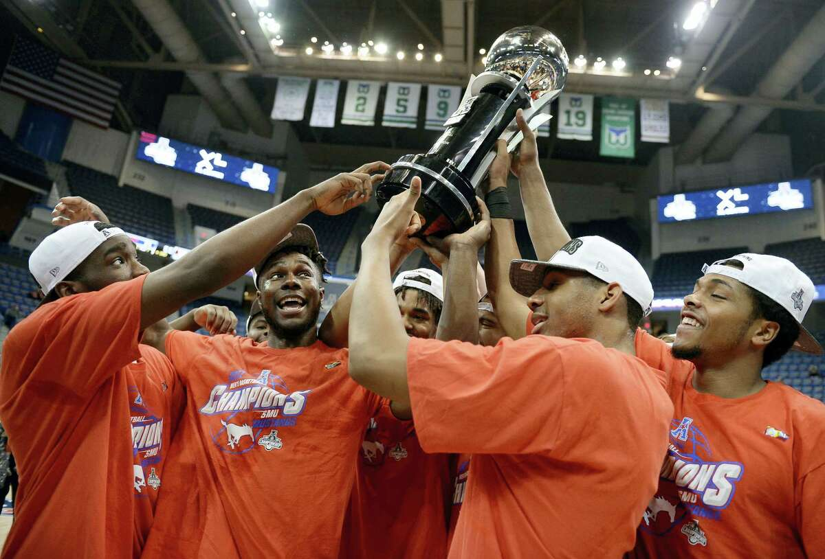 Members of the SMU men's basketball team hold up the American Athletic Conference championship trophy after their win Sunday in Hartford.