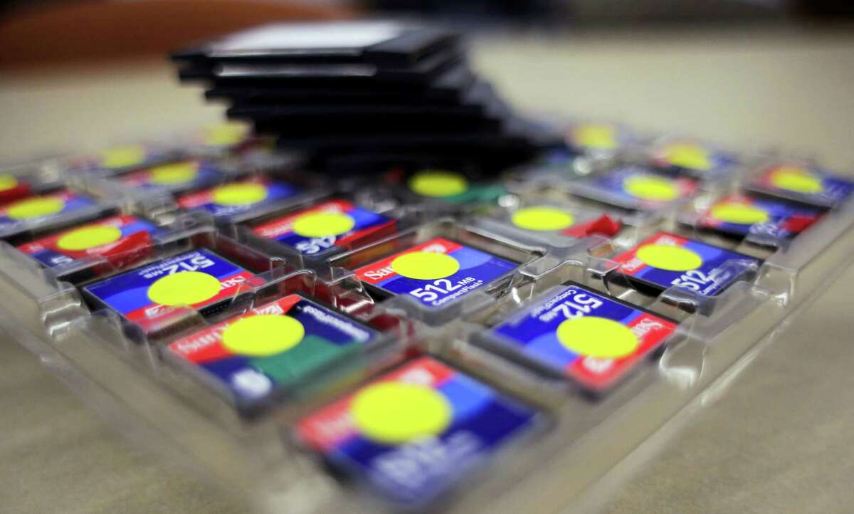 In this Thursday, March 9, 2017 photo, a stack of zip disks and a tray of compact flash cards sit at the Bexar County Elections office, in San Antonio. Bexar County's voting equipment is among the oldest in America's second-largest state and will have to be replaced soon. But money to do so is scarce and that scenario is playing out around the country. (AP Photo/Eric Gay)