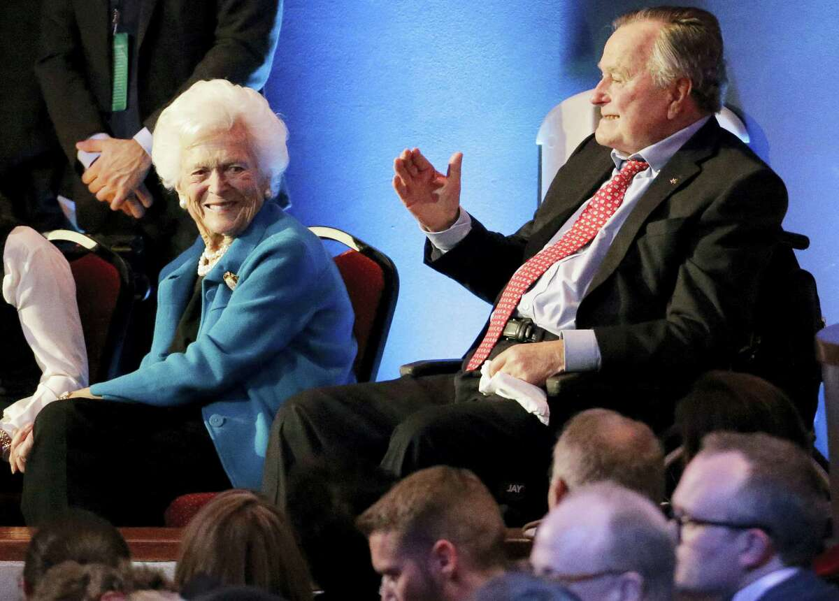 Former President George H. W. Bush, right, and his wife, Barbara, are greeted before a Republican presidential primary debate at The University of Houston in Houston in 2016.