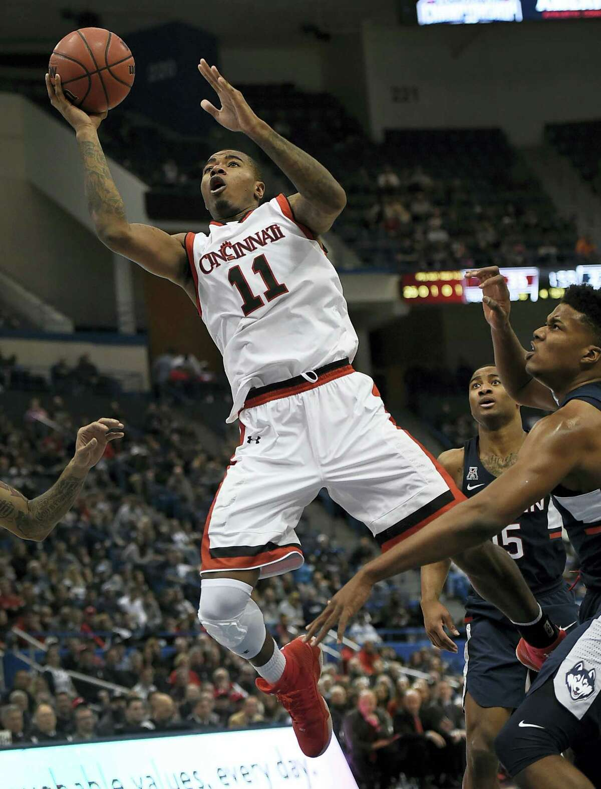 Cincinnati's Gary Clark, shoots as UConn's Vance Jackson, right, defends during the first half Saturday.
