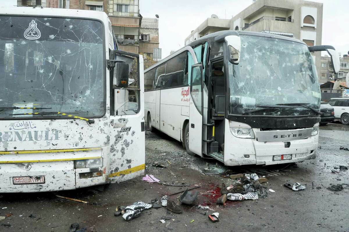 In this photo released by the Syrian official news agency SANA shows blood soaked streets and several damaged buses in a parking lot at the site of an attack by twin explosions in Damascus, Syria, Saturday, March 11, 2017. Twin explosions Saturday near religious shrines frequented by Shiite pilgrims in the Syrian capital Damascus killed dozens of people, Arab media and activists report.