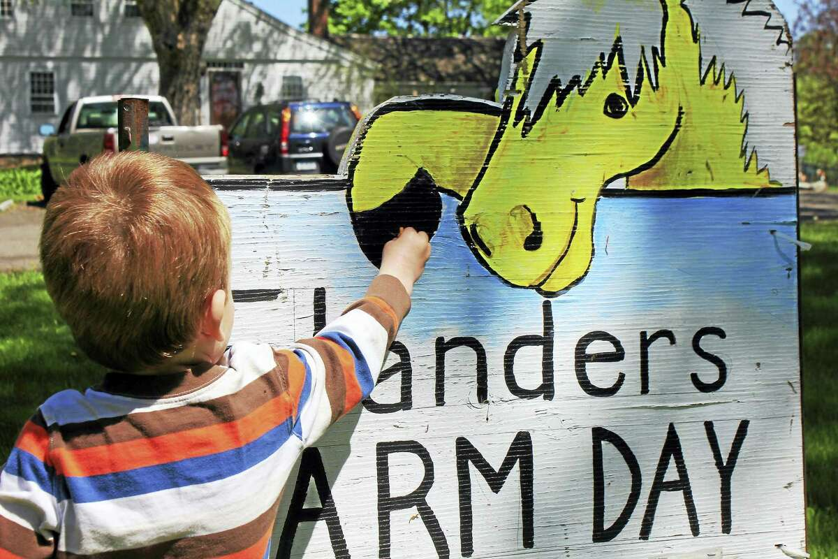 A child reaches for the farm day welcome sign during last year's event. Farm Day is set for Saturday at the nature center in Woodbury.