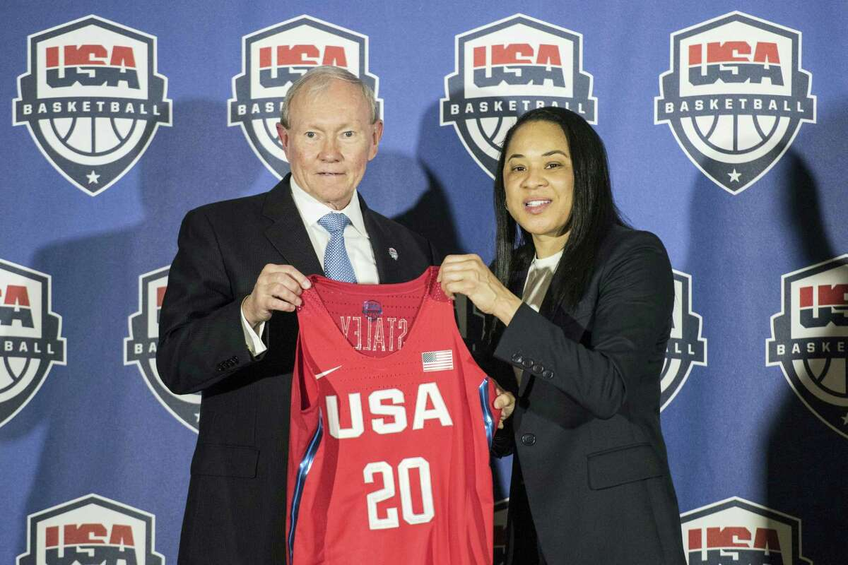 National Basketball Chairman Gen. Martin Dempsey, left, presents a jersey to South Carolina women's head basketball coach Dawn Staley, right, during a press conference on Friday.