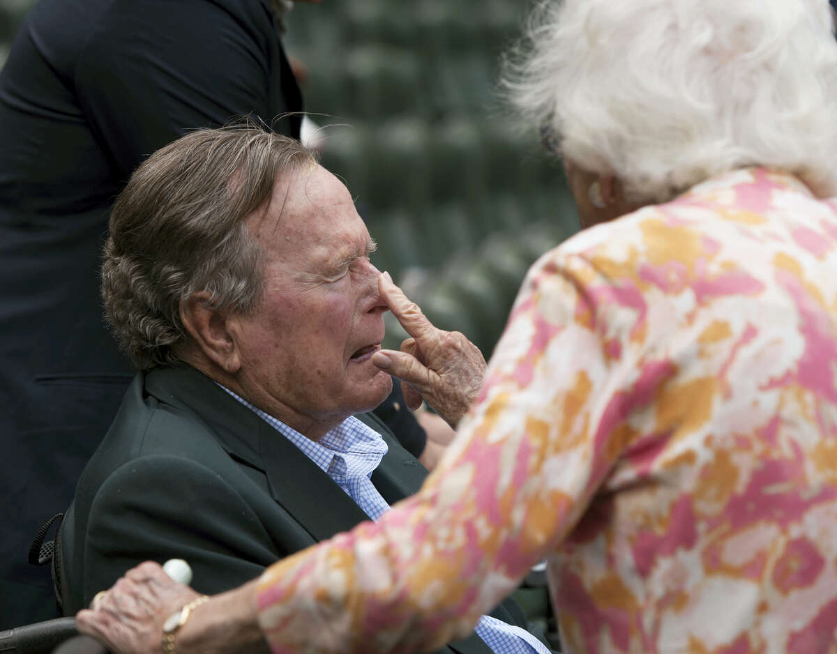 Barbara Bush applies sunscreen to the nose of her husband, former President George H.W. Bush, before the Seattle Mariners take on the Houston Astros in a baseball game in Houston, Texas in 2015.