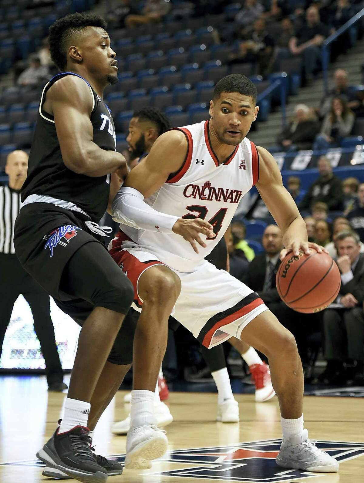 Cincinnati's Kyle Washington dribbles around Tulsa's Martins Igbanu.
