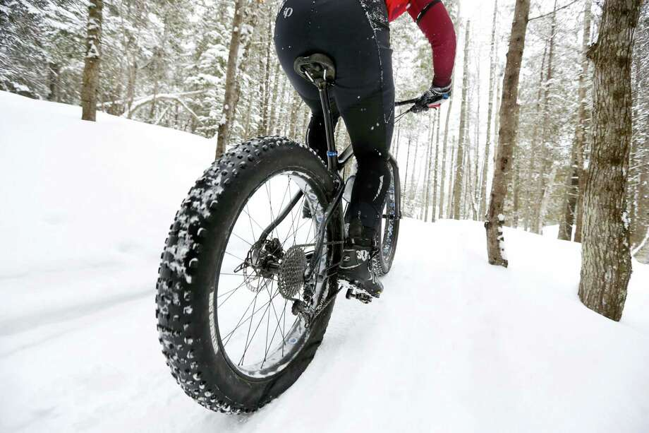 "In this Saturday, Feb. 11, 2017, photo a fat tire bicyclist rides on a cross country ski trail during a race at the Sugarloaf ski resort in Carrabassett Valley, Maine. Gone are the days when cyclists had to hang up their bikes the winter. These days, many of them are grinding through winter's snow and spring's mud thanks to trendy new ""fat bikes"" with extra wide tires. Photo: AP Photo/Robert F. Bukaty   / Copyright 2017 The Associated Press. All rights reserved."
