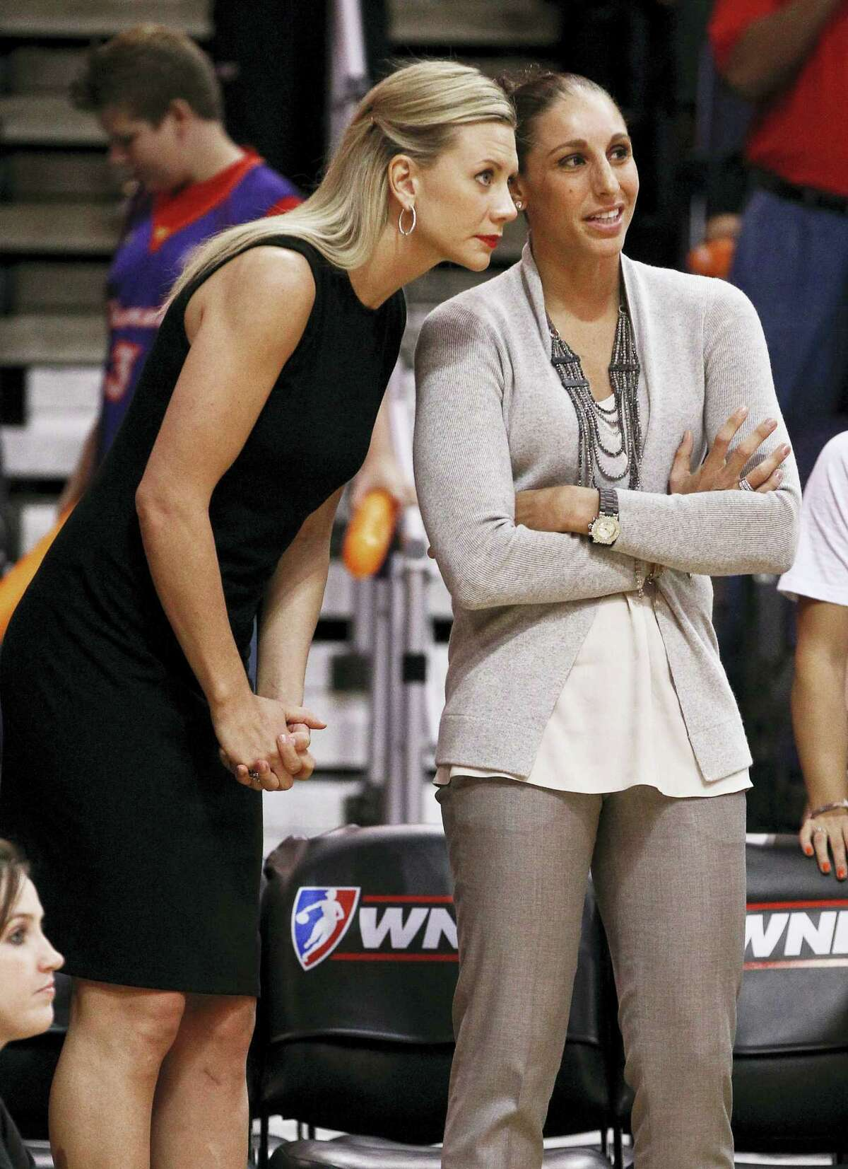 In this Sept. 12, 2012 photo, injured Phoenix Mercury players Penny Taylor, left, of Australia, and Diana Taurasi stand at the team bench during the first half of a WNBA basketball game against the Connecticut Sun, in Phoenix. Diana Taurasi has married former Phoenix Mercury teammate Penny Taylor, then played in the team's season opener less than 24 hours later. The 34-year-old Taurasi has played for the Mercury since 2004, helping the team win three titles. She also helped the U.S. win four consecutive Olympic gold medals. The couple married May 13, 2017.