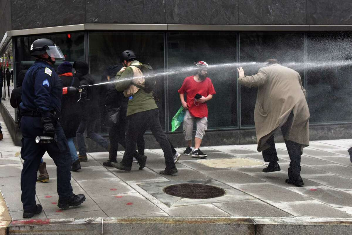A man is pepper sprayed at the corner of 12th and I St. N.W. in Washington on Jan. 20. Police responded to a vandalizing group of protesters with pepper spray to disperse the protesters.