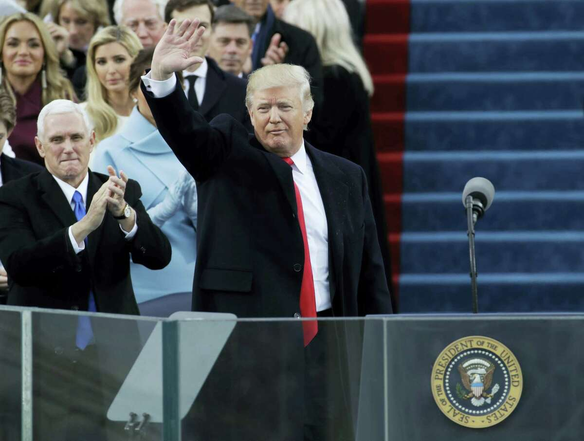 Vice President Mike Pence, left, applauds as President Donald Trump waves after delivering his inaugural address after being sworn in as the 45th president of the United States during the 58th Presidential Inauguration at the U.S. Capitol in Washington on Friday.