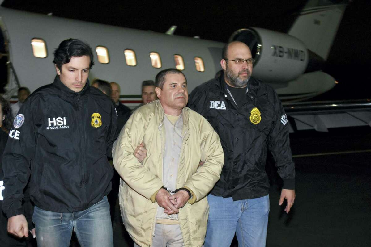 """In this photo provided U.S. law enforcement, authorities escort Joaquin """"El Chapo"""" Guzman, center, from a plane to a waiting caravan of SUVs at Long Island MacArthur Airport on Thursday, Jan. 19, 2017, in Ronkonkoma, N.Y."""