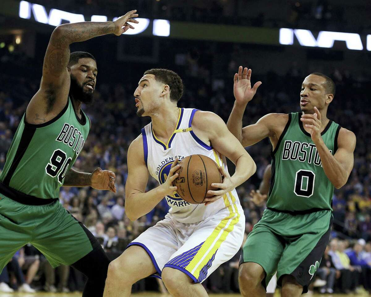 Golden State Warriors' Klay Thompson, center, looks for a shot between Boston Celtics' Amir Johnson, left, and Avery Bradley during the first half of an NBA basketball game March 8, 2017 in Oakland, Calif.