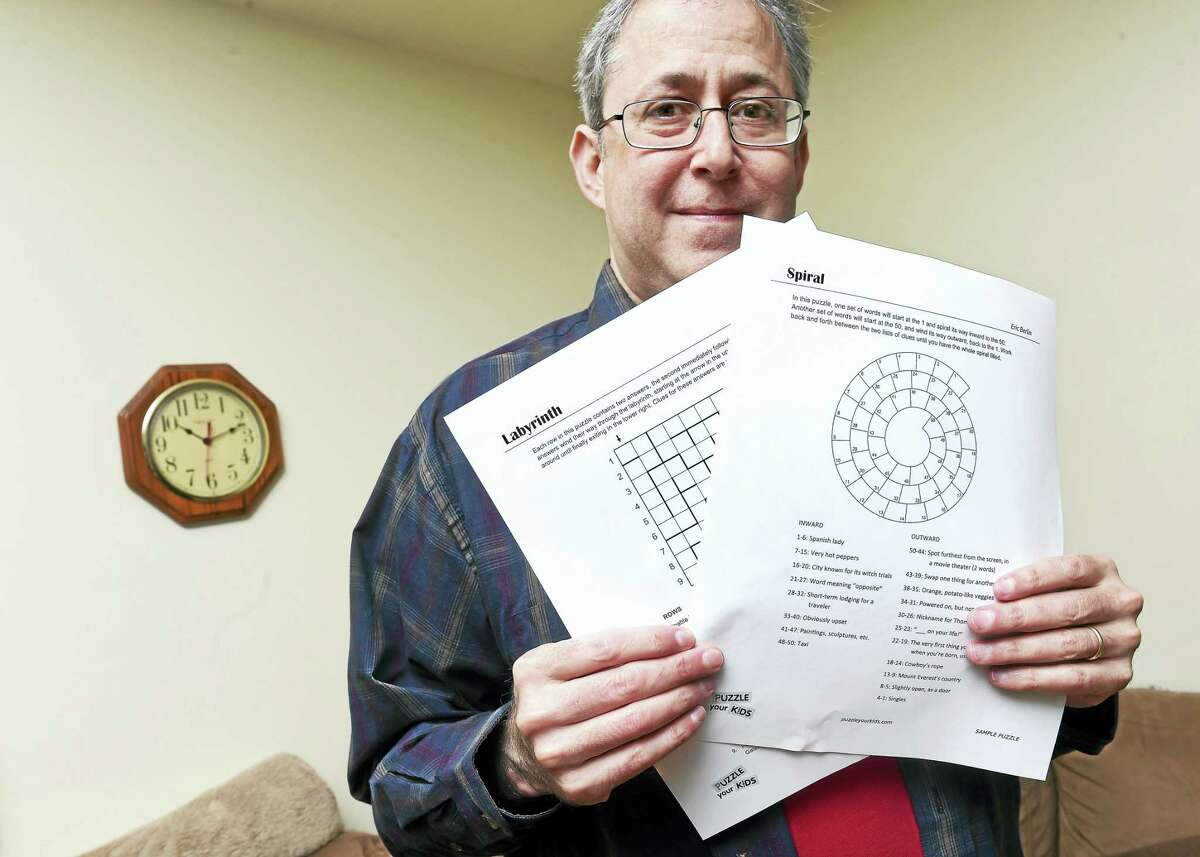 Eric Berlin displays a few of his word puzzles at his home in Milford earlier this month.