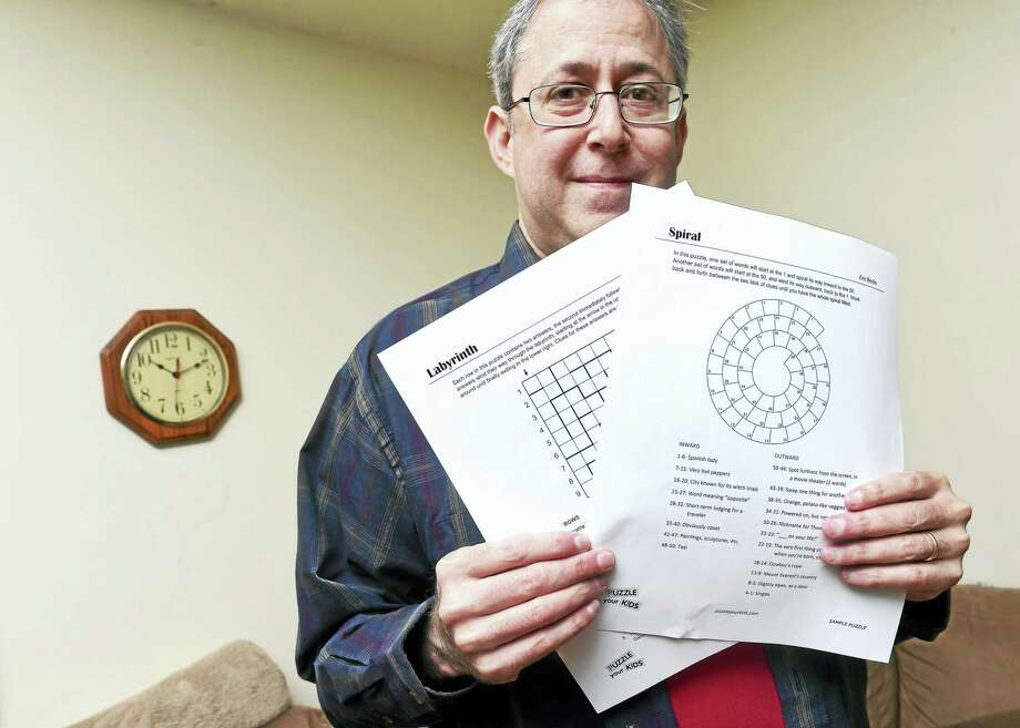 Eric Berlin displays a few of his word puzzles at his home in Milford earlier this month. Photo: ARnold Gold — New Haven Register