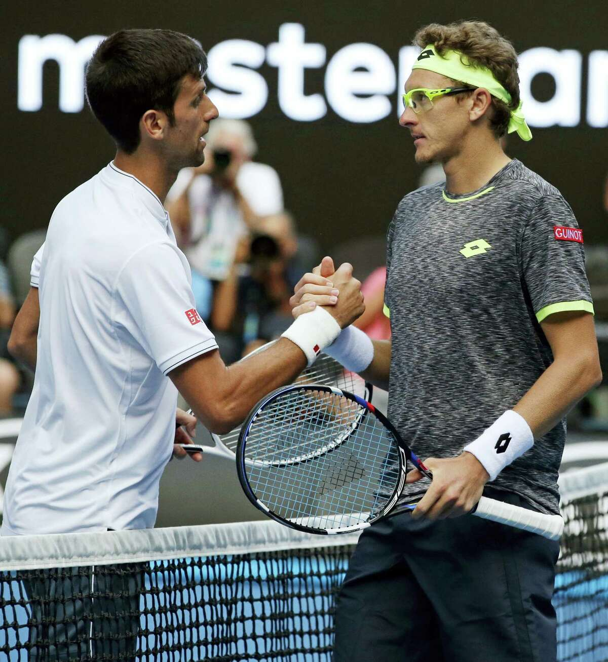 Uzbekistan's Denis Istomin, right, is congratulated by Serbia's Novak Djokovic after winning their second round match at the Australian Open tennis championships in Melbourne, Australia on Jan. 19, 2017.