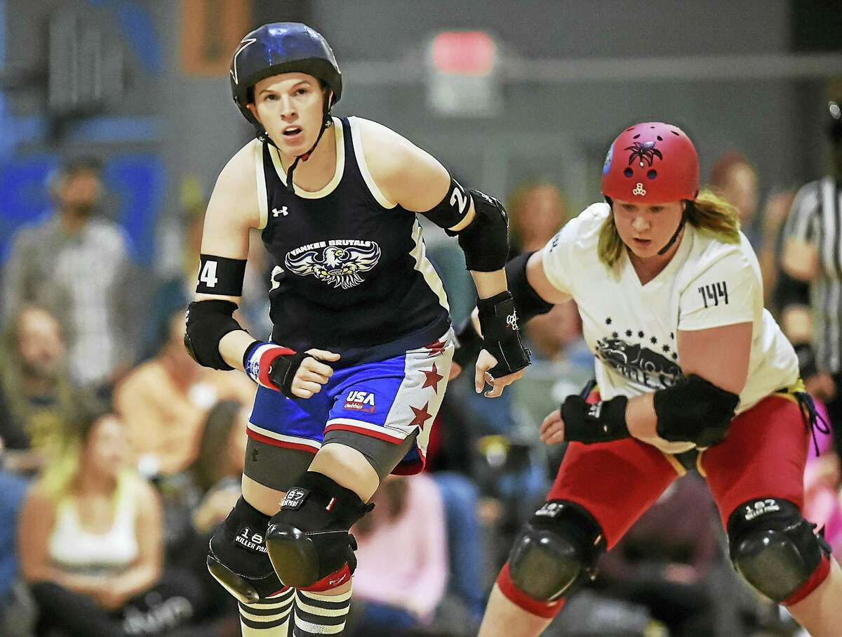 Kill-ty Pleasure, number 24, a jammer for the Yankee Brutals, racks up points while skating past number 144 Tigrr Killy, a blocker for the Battle Cats of New York, on a flat track at Insports in Trumbull.