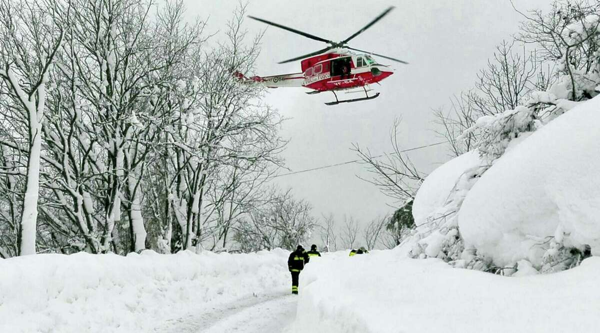 An Italian firefighters helicopter flies during rescue operations in the area where an hotel was hit by an avalanche in Farindola, Italy, early Thursday, Jan. 19, 2017. A hotel in the mountainous region hit again by quakes has been covered by an avalanche, with reports of dead. Italian media say the avalanche covered the three-story hotel in the central region of Abruzzo, on Wednesday evening.