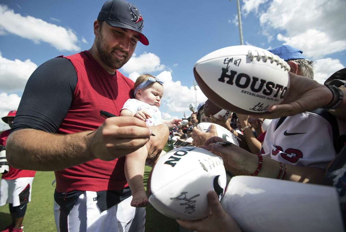 Texans quarterback Tom Savage holds his daughter, Summer, as he signs autographs following practice during training camp at The Methodist Training Center on Aug. 22, 2017, in Houston.