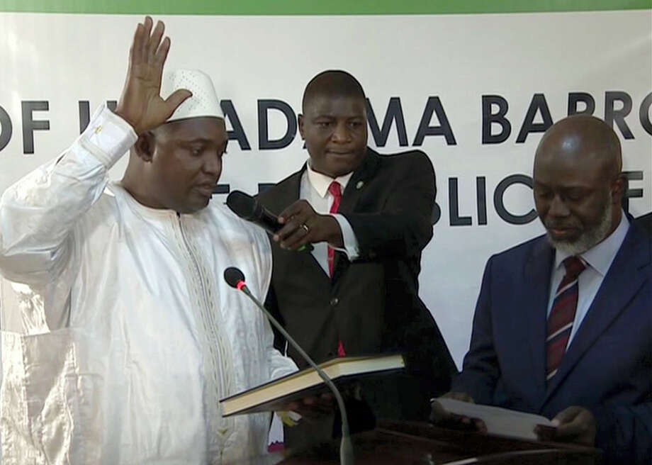 Adama Barrow, left, is sworn in as President of Gambia at Gambia's embassy in Dakar Senegal in this image taken from TV on Jan 19, 2017. A new Gambian president has been sworn into office in neighboring Senegal, while Gambia's defeated longtime ruler refuses to step down from power, deepening a political crisis in the tiny West African country. Photo: RTS Via AP  / Copyright 2017 The Associated Press. All rights reserved.