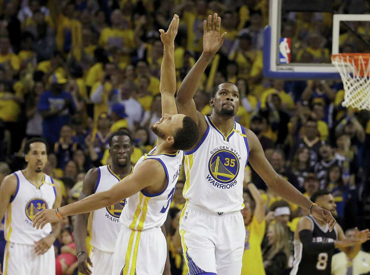Warriors guard Stephen Curry, center left, and forward Kevin Durant celebrate during the second half on Sunday.