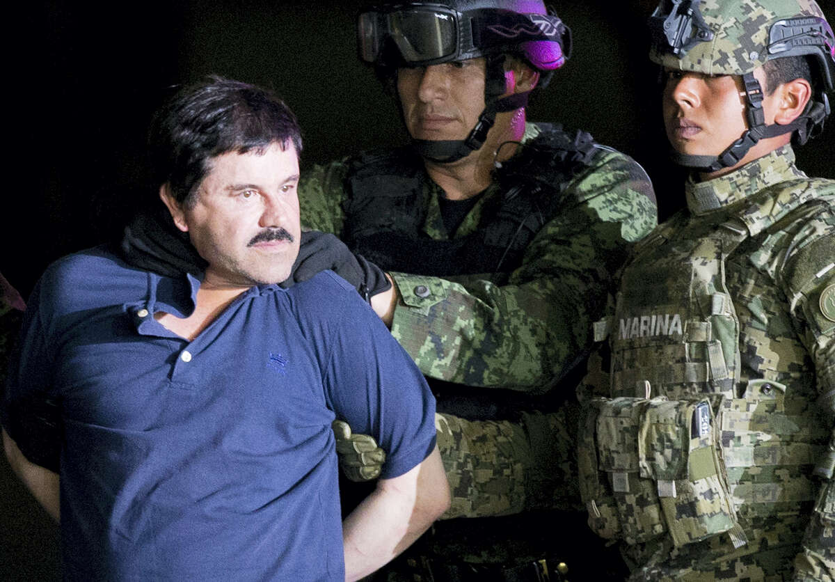 """A handcuffed Joaquin """"El Chapo"""" Guzman is made to face the press as he is escorted to a helicopter by Mexican soldiers and marines at a federal hangar in Mexico City last year."""
