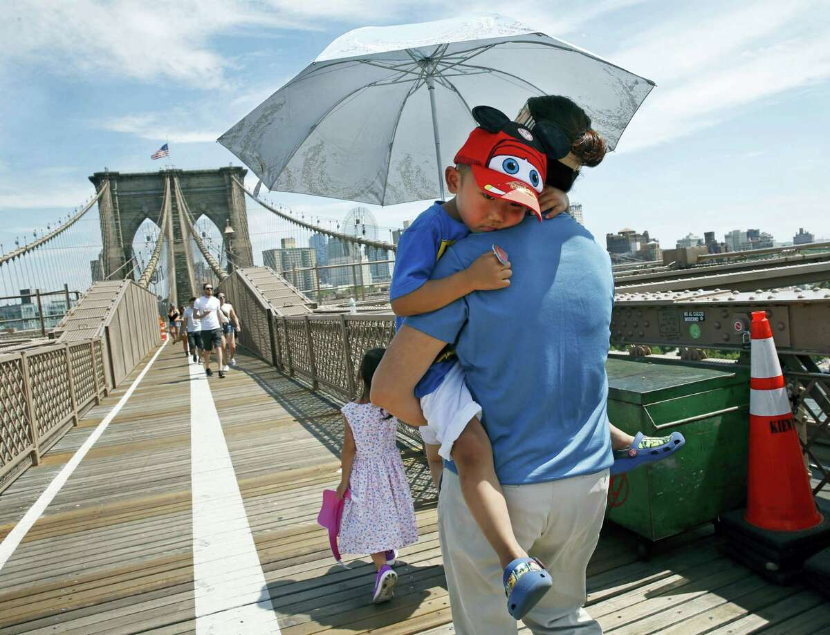 Xiuquin Huang carries her grandson Ruize Yan beneath an umbrella as she walks across the Brooklyn Bridge with her daughter and granddaughter Rina Wu last summer. For the third straight year, Earth set a record for the hottest year, NOAA and NASA announced.