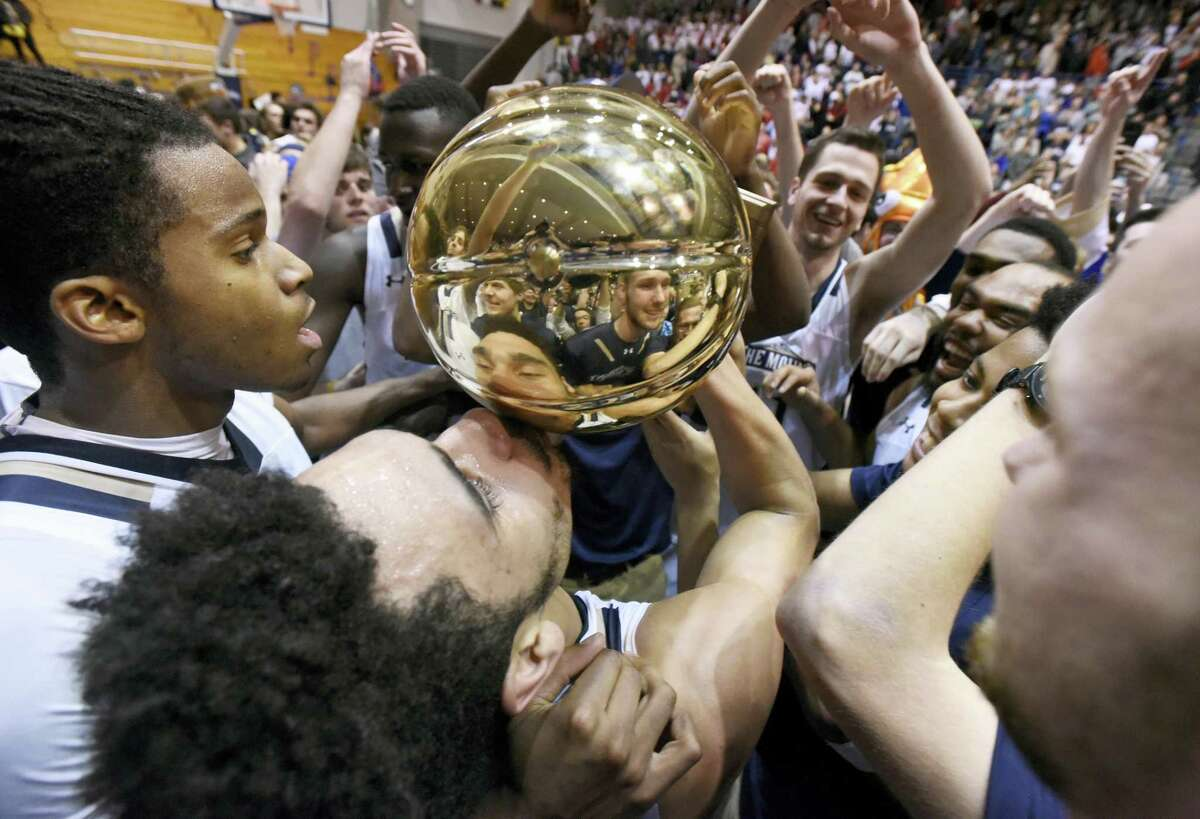 Mount St. Mary's guard Elijah Long, center, kisses the Northeast Conference Tournament championship trophy after beating St. Francis (Pa.) 71-61 in the Northeast Conference Tournament championship game Tuesday.