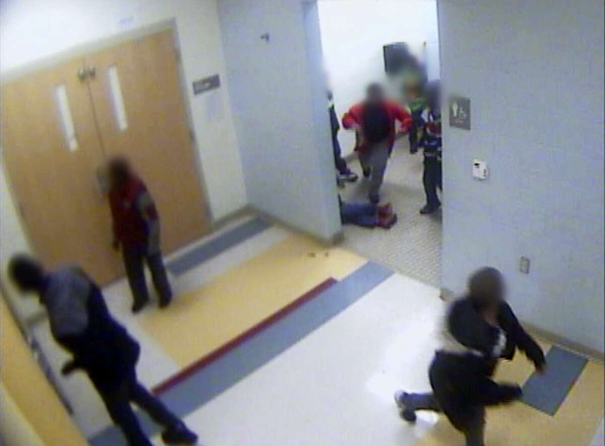 In this still image from a Jan. 24, 2017, surveillance video provided by Cincinnati Public Schools, the legs and feet of 8-year-old Gabriel Taye can be seen as he lies on the floor of a boys' bathroom after being knocked unconscious by another boy at Carson Elementary School. Two days later, Taye hanged himself with a necktie in the bedroom of his Cincinnati apartment.