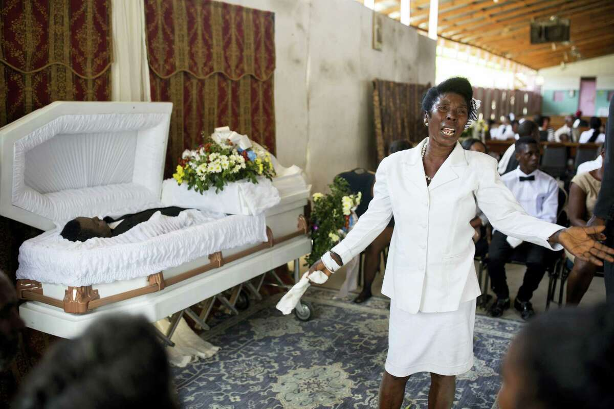 A woman cries during the funeral of her son at the St. Anne Church in Port-au-Prince, Haiti. While many Haitians pool resources and seek funeral expenses from relatives living overseas, there's no shortage of grief-stricken families who sell possessions or take out high-interest-rate loans, in part due to deep traditions for open-casket funerals and social pressures to bury loved ones with a splash.