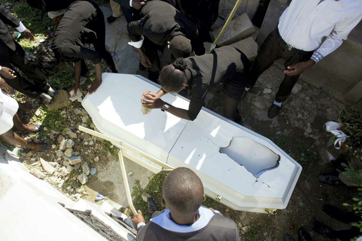 Relatives damage the coffin with the remains of a family member, right before burial at the national cemetery in Port-au-Prince, Haiti. They damaged the brand new coffin in order to prevent it from being stolen and the body dumped out into the ground.