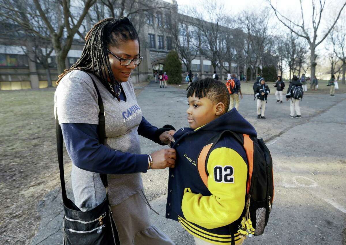 In this Feb. 23, 2017, photo, Natalie Langlaise snaps the jacket of her son Justin outside the Martin Luther King Jr. Elementary School in Hartford, Conn. The city of Hartford has been hailed nationally as a school choice success story. Its magnet schools have promoted racial integration and new levels of academic achievement. For traditional public schools, such as Martin Luther King Jr., it's a different story.