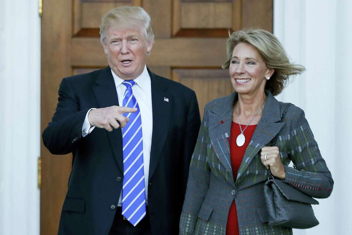 President-elect Donald Trump stands with Education Secretary-designate Betsy DeVos in Bedminster, N.J. DeVos has spent over two decades advocating for school choice programs, which give students and parents an alternative to traditional public school education. Her confirmation hearing was scheduled for Jan. 17.