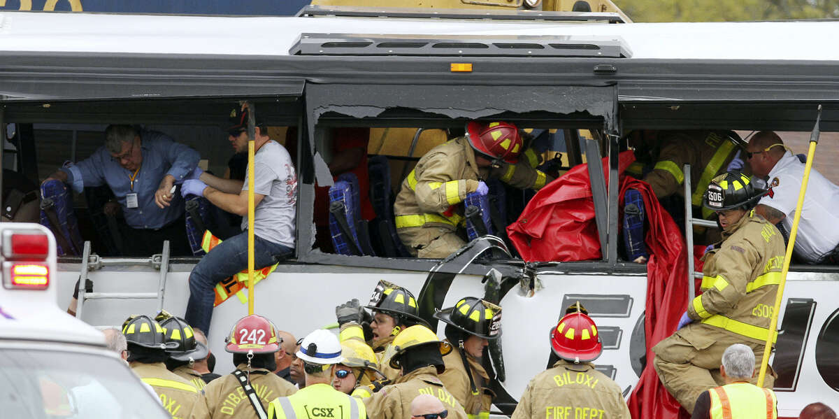Rescue personnel work to remove passengers from a charter bus that was hit by a CSX train at the Main Street crossing in Biloxi, Miss., on Tuesday, March 7, 2017.The bus was carrying 50 people from Austin, Texas, Biloxi Police Chief John Miller said at a news conference. He said authorities believe the bus was stopped on the tracks at the time of the crash, but they don't yet know why. ( John Fitzhugh/The Sun Herald via AP)