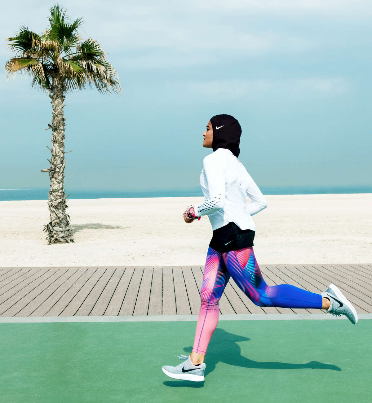 In this undated image provided by Nike, Manal Rostom jogs wearing Nike's new hijab for Muslim female athletes. The pull-on hijab is made of light, stretchy fabric that includes tiny holes for breathability and an elongated back so it will not come untucked. It will come in three colors: black, vast grey and obsidian. Beaverton-based Nike says the hijab will be available for sale next year.