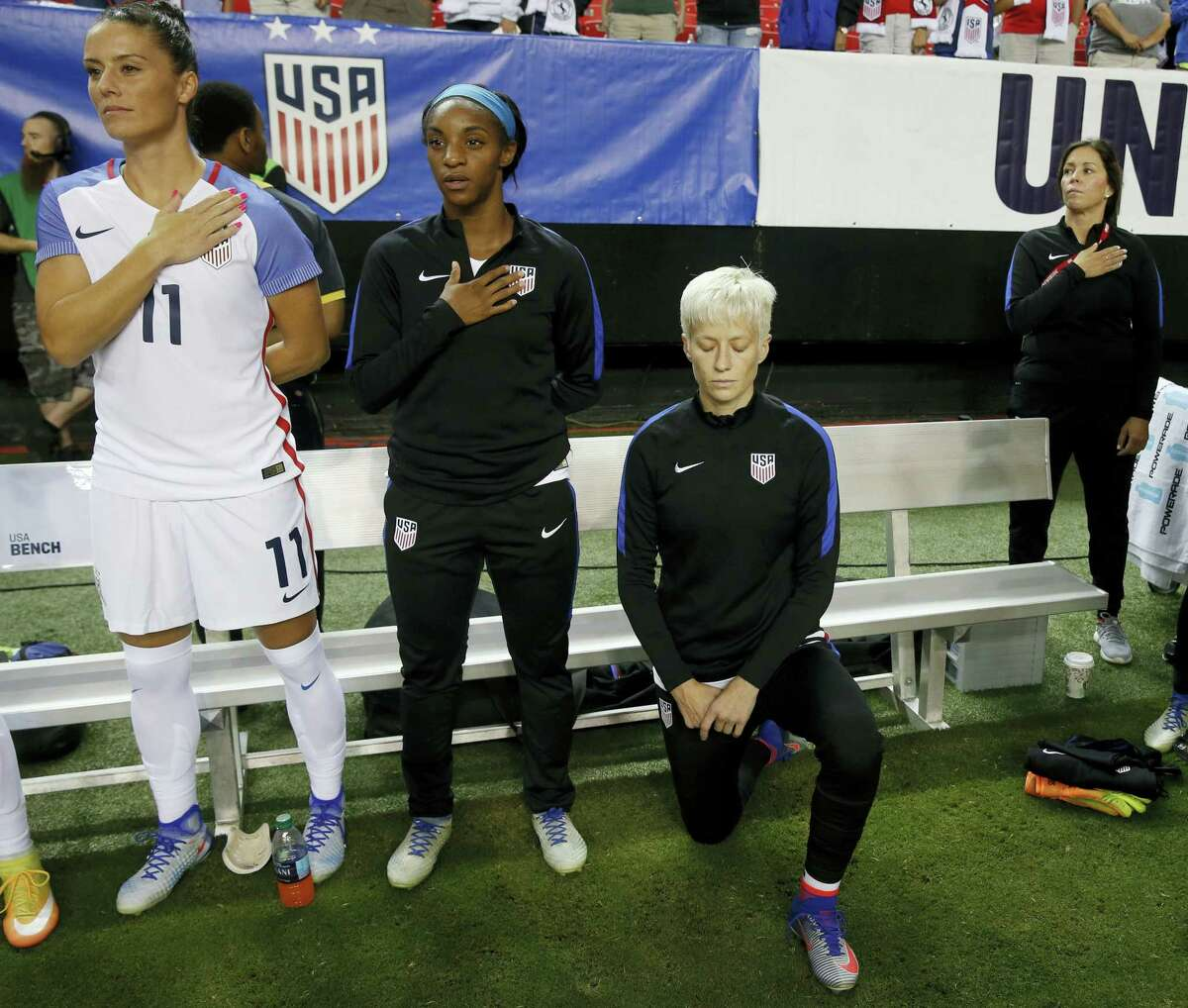 """the United States' Megan Rapinoe, right, kneels next to teammates Ali Krieger (11) and Crystal Dunn (16) as the U.S. national anthem is played before an exhibition match. Rapinoe says she will respect a new U.S. Soccer Federation policy that says national team players """"shall stand respectfully"""" during national anthems."""