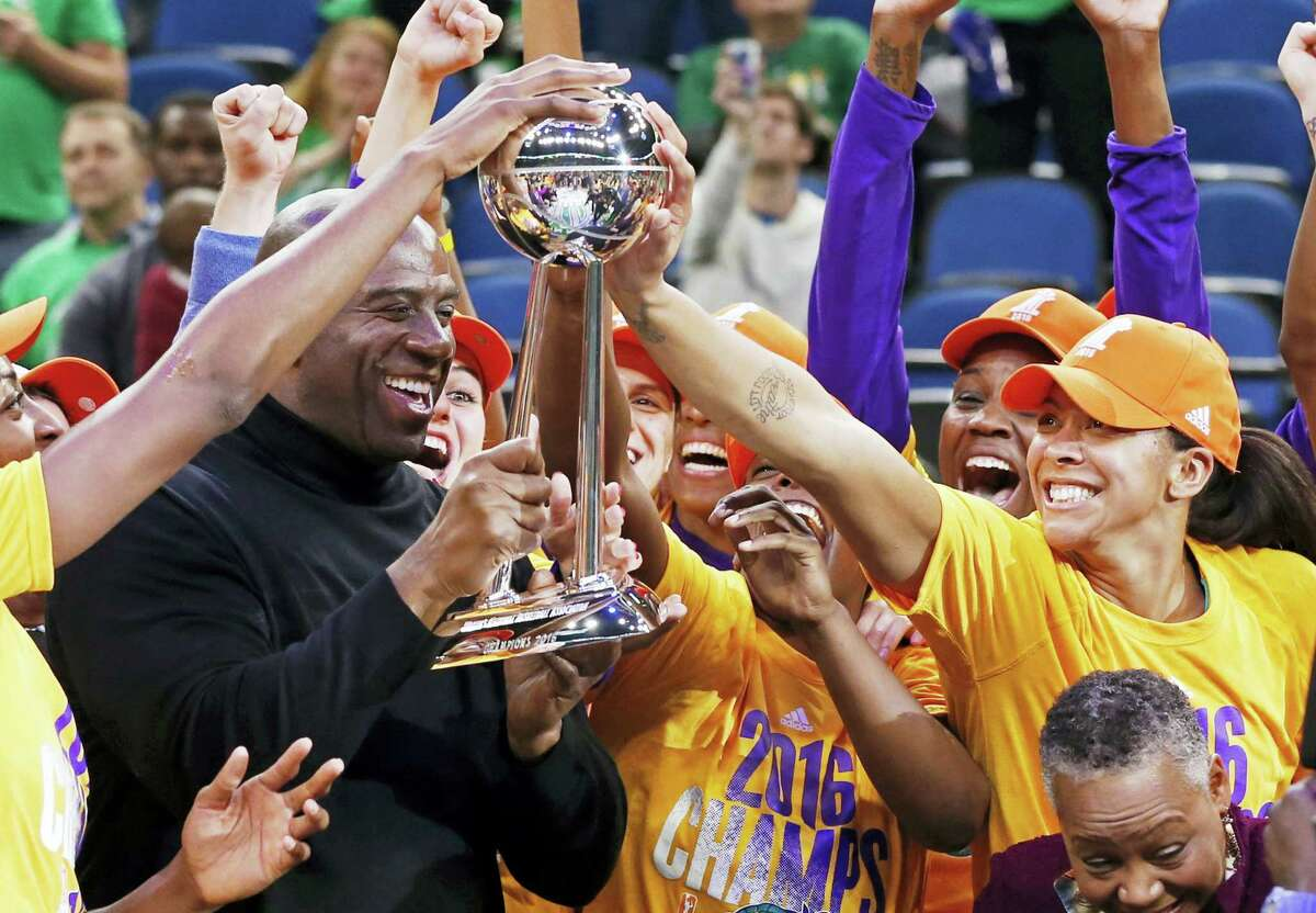 In this Oct. 20, 2016 photo, Los Angeles Sparks' Candace Parker, right, touches the trophy held by team owner Magic Johnson after the Sparks won the WNBA championship title with a win over the Minnesota Lynx in Game 5 in Minneapolis. The defending champion Los Angeles Sparks start the season atop The Associated Press WNBA poll.