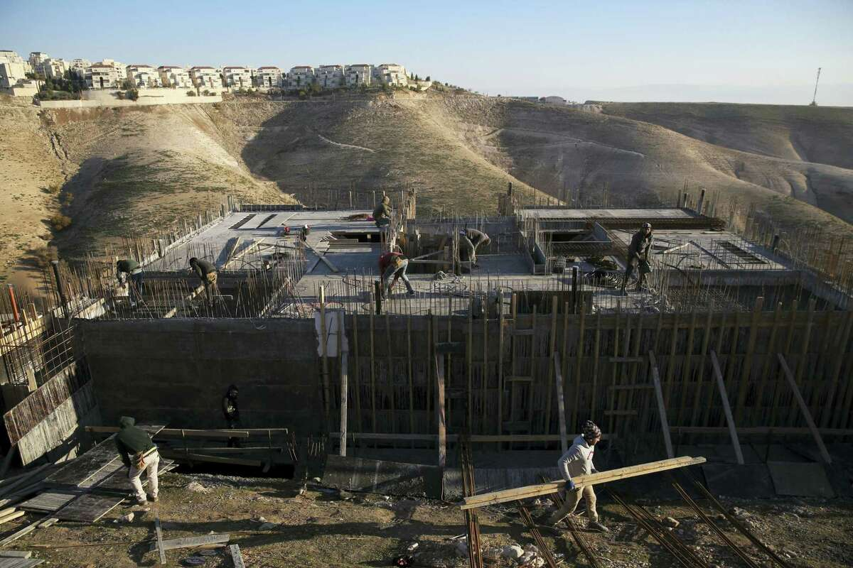 """This Feb. 7, 2017 photo shows Palestinian laborers work at a construction site in a new housing project in the Israeli settlement of Maale Adumim, near Jerusalem. Israel's defense minister says the U.S. has notified Israel that imposing Israeli sovereignty over the West Bank would lead to an """"immediate crisis"""" with the Trump administration. Defense Minister Avigdor Lieberman said March 6, 2017 that, """"We received a direct message — not an indirect message and not a hint — from the United States. Imposing Israeli sovereignty on Judea and Samaria would mean an immediate crisis with the new administration."""""""