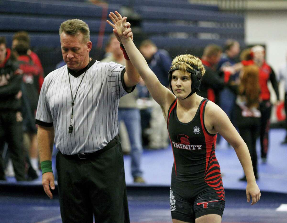 In this Feb. 18, 2017 photo, Euless Trinity's Mack Beggs is announced as the winner of a semifinal match after Beggs pinned Grand Prairie's Kailyn Clay during the finals of the UIL Region 2-6A wrestling tournament at Allen High School in Allen, Texas. Beggs, a transgender boy who won a girls wrestling state title in Texas, says he would compete against boys if allowed and is taking lower doses of testosterone to try to be fair to his opponents.