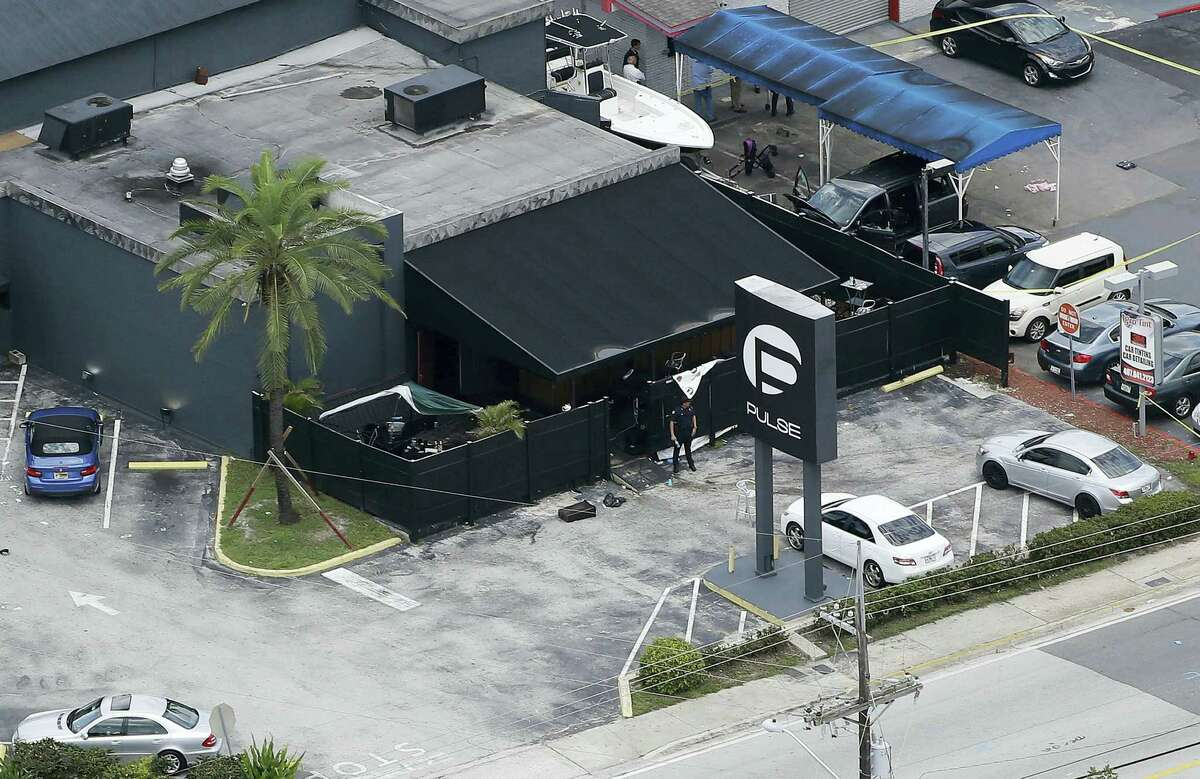 In this file photo, law enforcement officials work at the Pulse gay nightclub in Orlando, Fla., following the a mass shooting. Audio recordings of 911 calls released Tuesday, Aug. 30, by the Orange County Sheriff's Office show mounting frustration by friends and family members who were texting, calling and video-chatting with trapped patrons of the Pulse nightclub where Omar Mateen opened fire in June. A U.S. law enforcement official says the FBI has arrested the wife of the Orlando nightclub shooter. The official says Noor Salman was taken into custody Monday in the San Francisco area and is due in court Tuesday in California. She's facing charges in Florida including obstruction of justice.