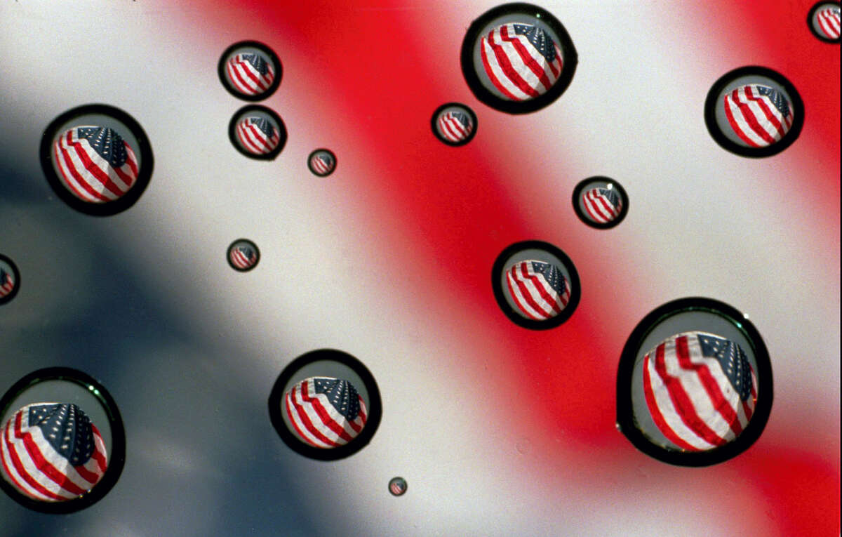 In this Nov. 10, 1997 file photo,a U.S. flag refracted in water drops on a car windshield in Gorham, Maine. The vast majority of Americans fear the country is losing its identity, but underlying that widespread agreement is equally deep disagreement over what it means to be an American. A new poll from The Associated Press-NORC Center for Public Affairs Research finds the country is torn over what poses the greatest threat to the national way of life.