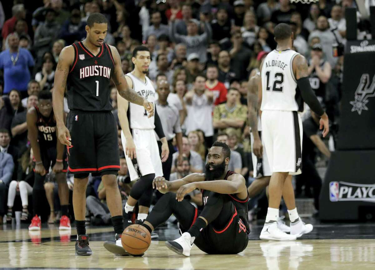 Houston Rockets' James Harden (13) sits on the court as Trevor Ariza (1) walks over during overtime of Game 5 in a second-round NBA basketball playoff series against the San Antonio Spurs on May 9, 2017 in San Antonio. San Antonio won 110-107.