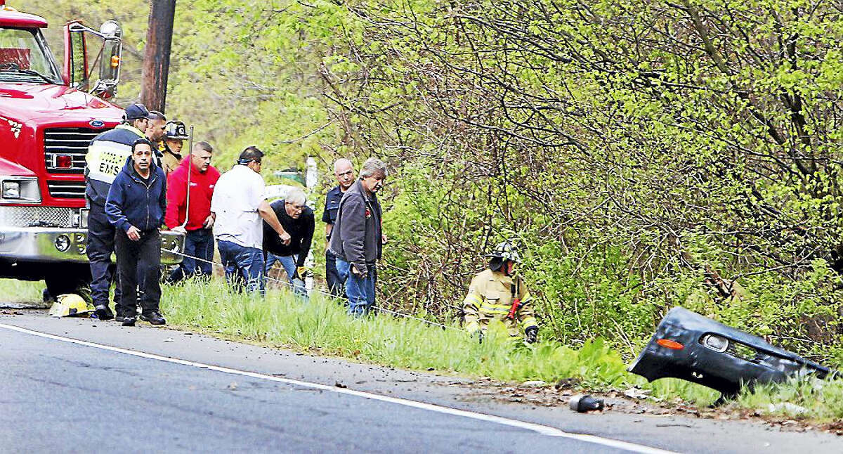 In this May 9, 2017, photo, firefighters try to secure a vehicle that went into a stream during a motor vehicle accident in Woodbury. Katherine Ann Berman, wife of longtime ESPN broadcaster Chris Berman, died in the crash.