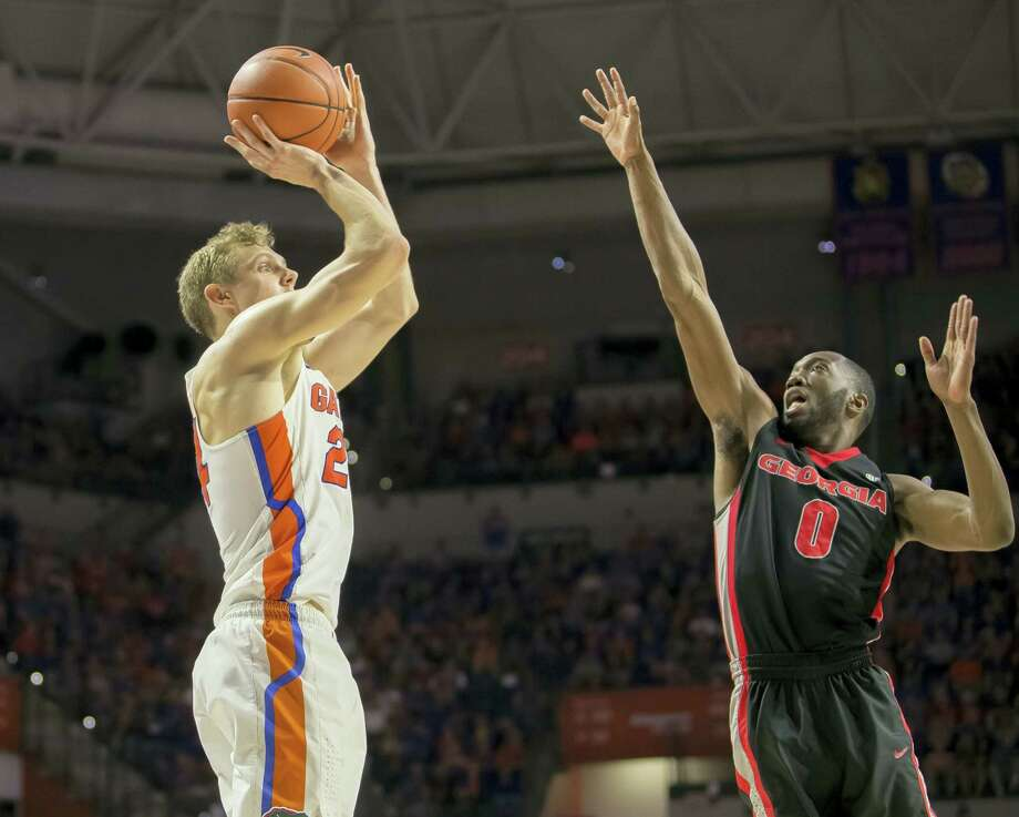 Florida guard Canyon Barry, left, shoots over Georgia guard William Jackson II during a recent game. Photo: The Associated Press File Photo  / FR171372 AP