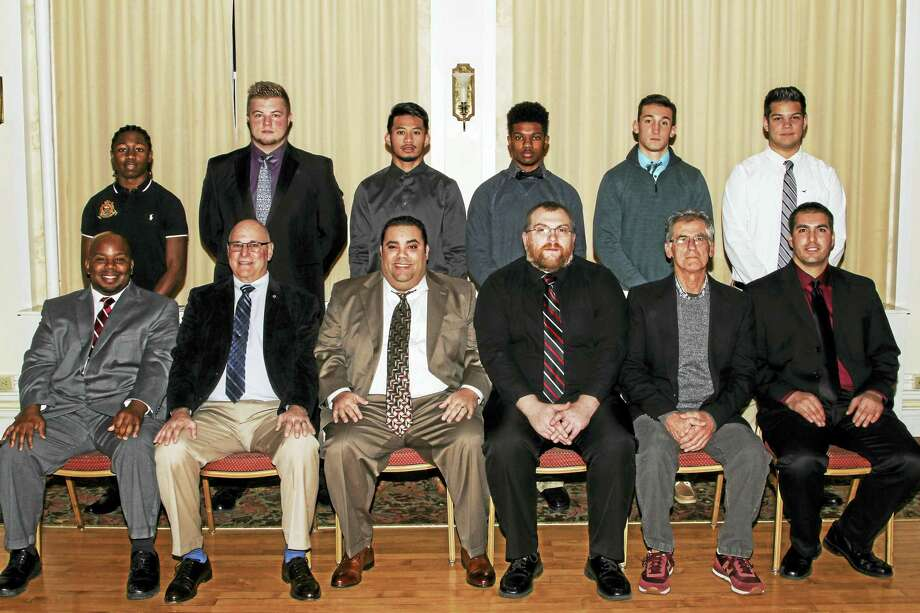 Torrington football coaches and seniors at the team's annual banquet Sunday night at the Torrington Elks Club were, seated, left to right defensive line coach Cortney Dunlap; offensive coordinator Don Whitley; head coach Gaitan Ridriguez; line coach Andy Therriault; defensive coordinator Bob Reynolds; freshman coach Kevin Caruso. Standing, left to right, seniors Jermaine Reese, Andrew Schimanski, Dom Phenkaen, Tory Hammonds, Justin Egliskis, Rudi Patai. Photo: Photo By Marianne Killackey  / 2015