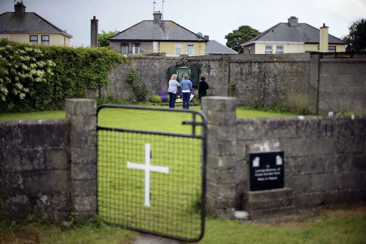 In this June 7, 2014, file photo members of the public at the site of a mass grave for children who died in the Tuam mother and baby home, in Tuam, County Galway. Forensics experts say they have found a mass grave for young children at a former Catholic orphanage in Ireland where suspicions of unrecorded, unmarked burials have lingered for decades.