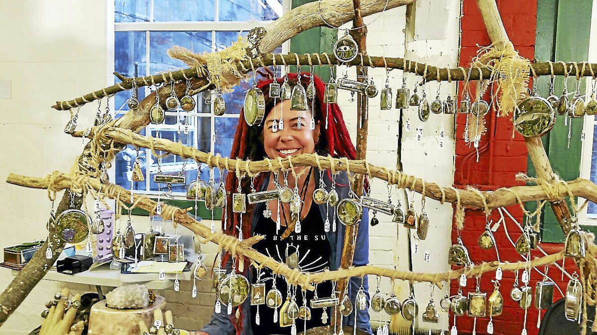 Kerrie Ogren, proprietor of The Wild Fay, exhibits and her homemade jewelry and ecology-inspired art at a display table Sunday.