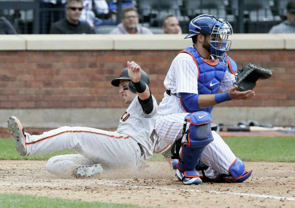 San Francisco's Buster Posey slides past New York Mets catcher Kevin Plawecki to score on a double by Christian Arroyo during the ninth inning. The Giants rallied to beat the Mets 6-5.