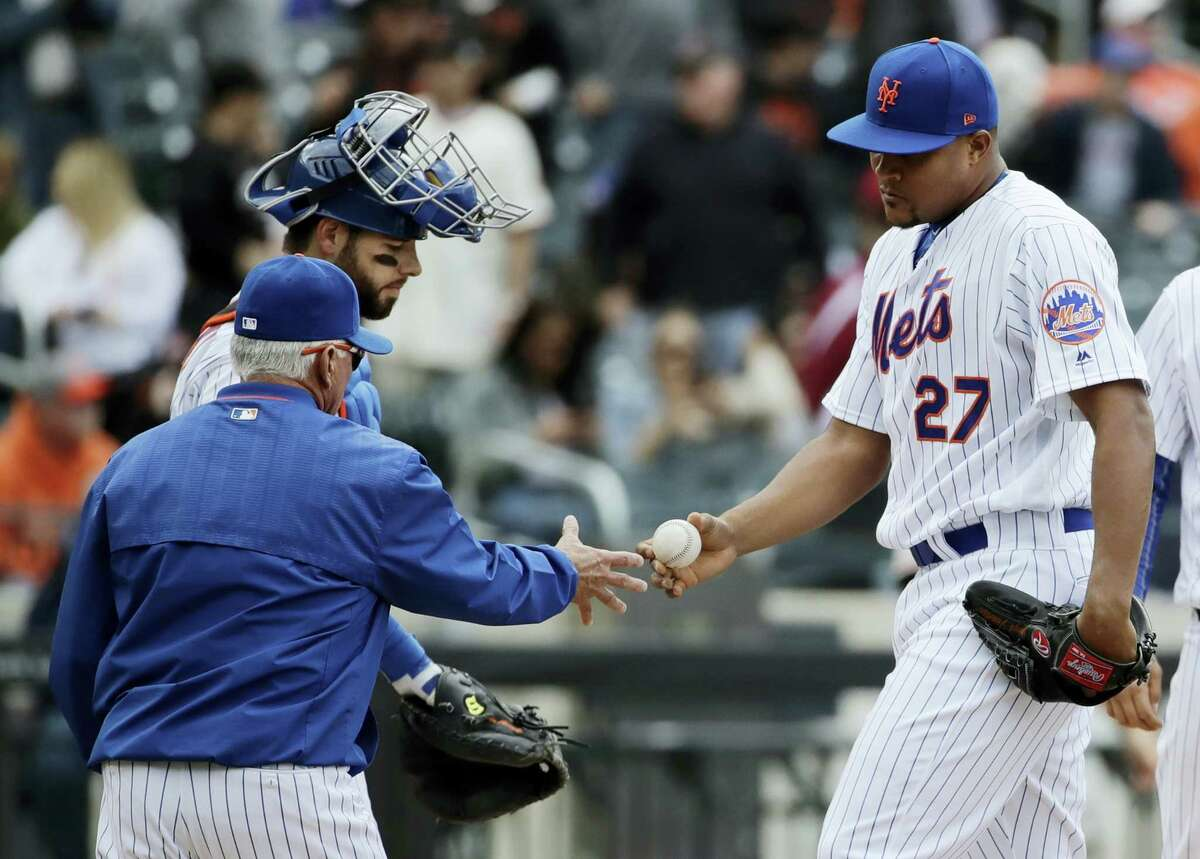 New York Mets relief pitcher Jeurys Familia hands the ball to manager Terry Collins as catcher Kevin Plawecki looks on during the top of the ninth inning.