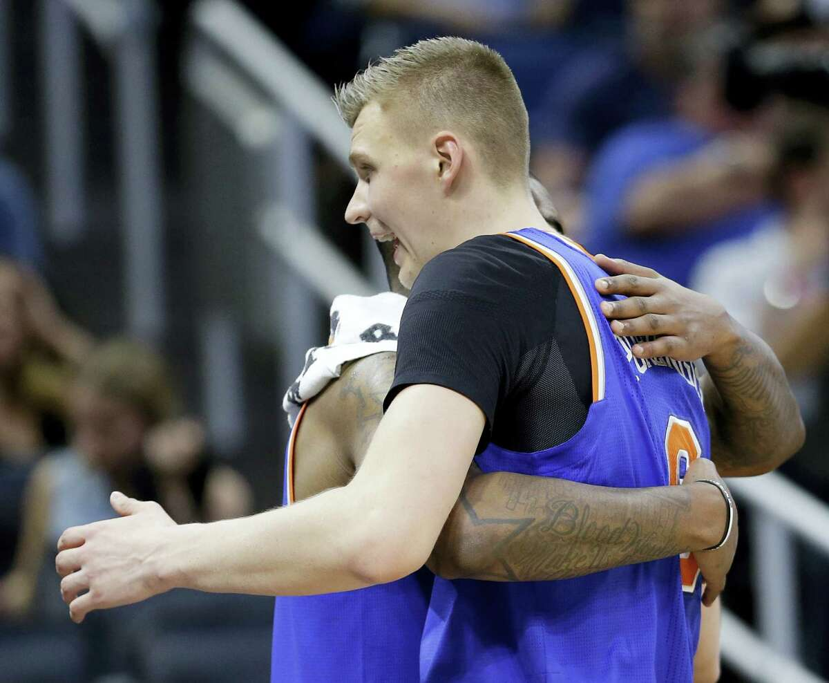 New York Knicks' Kristaps Porzingis, right, gets a hug from teammate Kyle O'Quinn as he comes off the court during the final moments of an NBA basketball game on March 1, 2017 in Orlando, Fla. New York won 101-90.