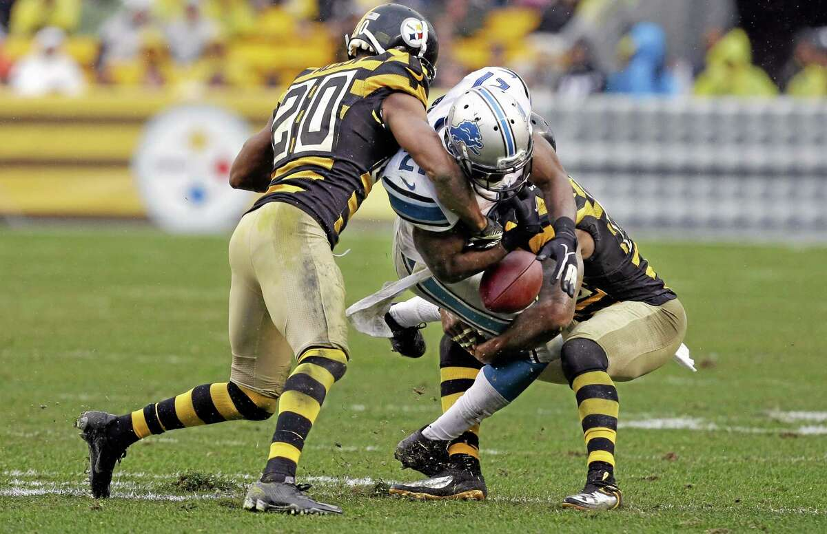AP Photo — Gene J. Puskar Detroit Lions running back Reggie Bush (21) loses the football as Pittsburgh Steelers strong safety Will Allen (20) and free safety Ryan Clark (25) hit him in the first half of an NFL football game in Pittsburgh, on Nov. 17, 2013. The play was called dead on an early whistle and no fumble was ruled.