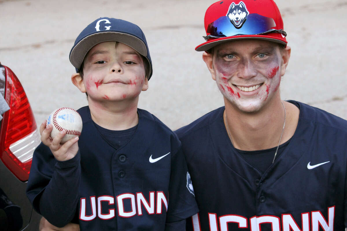 In this photo provided by the Hand family, Grayson Hand, left, poses during a Halloween gathering with UConn pitcher Ryan Radue in Sturbridge, Mass.
